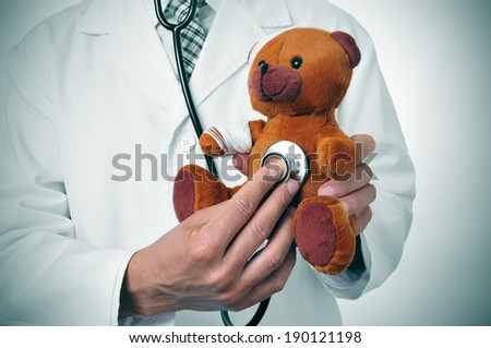 a doctor auscultating a teddy bear with bandages in its head and arm, depicting the pediatric medicine or the veterinary medicine concepts - stock photo