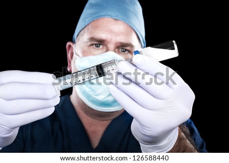 A doctor draws narcotics from a vial in preparation to inject a patient. - stock photo