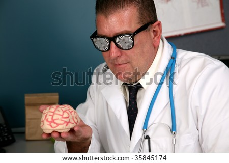 a doctor examines a human brain with his x-ray glasses - stock photo