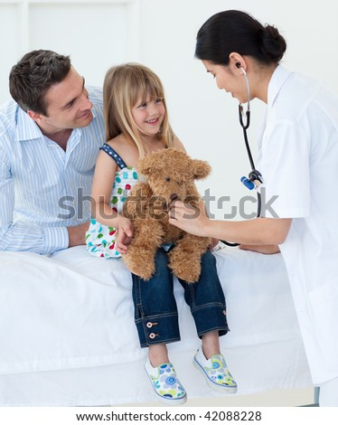 A doctor examining smiling child and playing with a teddy bear in the hospital - stock photo