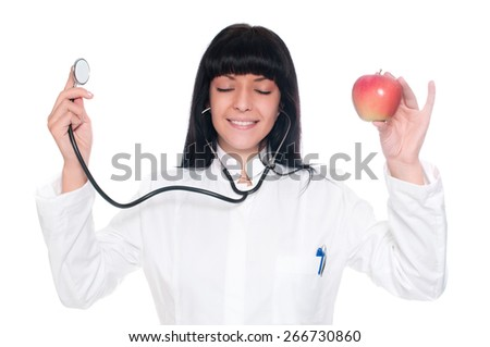 A doctor holding apples and stethoscope with eyes closed,