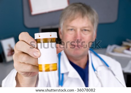 A doctor holds out a pill bottle used for prescriptions.  Label is blank for copy.  Good for pharmacy or pharmaceutical inferences. - stock photo