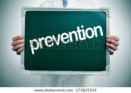 a doctor in white coat showing a chalkboard with the word prevention written in it - stock photo