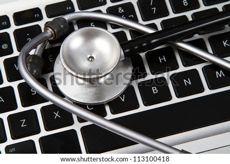 A doctor or nurses stethoscope on a computer keyboard. - stock photo