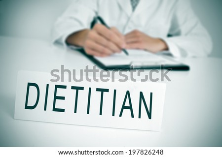 a doctor sitting in a desk with a nameplate in front of him with the word dietitian written in it - stock photo