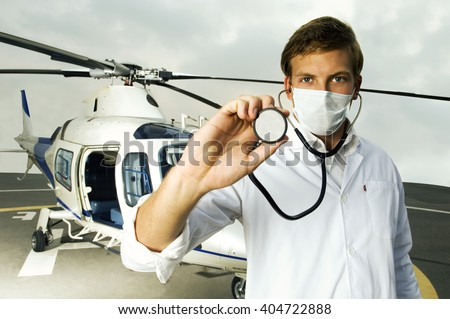 A doctor standing by a helicopter