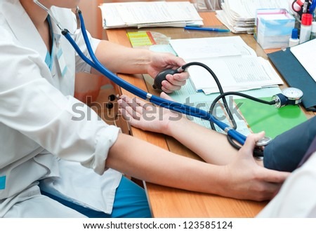 a doctor takes a patients blood pressure