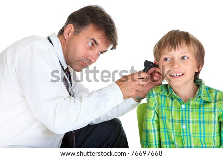 A doctor using a light device to examine inside the ear of a young boy.