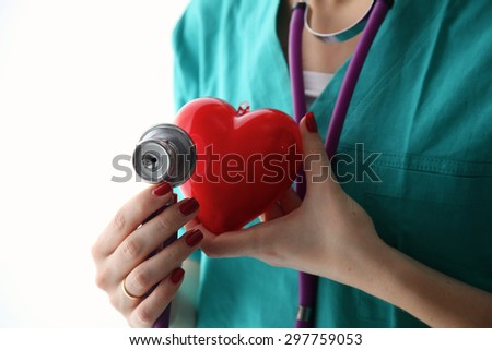 A doctor with stethoscope examining red heart .