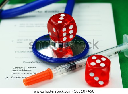 A Doctors desk with a dice placed on top of a blue stethoscope, with  another dice and insulin syringe all placed on a doctors sick certificate pad, asking the question, do you gamble with your health - stock photo