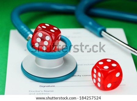 A Doctors desk with a dice placed on top of a blue stethoscope, with another dice placed on a doctors sick certificate pad, asking the question, do you gamble with your health - stock photo