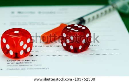 A Doctors desk with two dice placed next to an insulin syringe all placed on a doctors sick certificate pad, asking the question, do you gamble with your health.  - stock photo