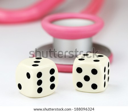 A Doctors Pink stethoscope with two white dice with black spots dice placed next to it, asking the question, do you gamble with your health. - stock photo