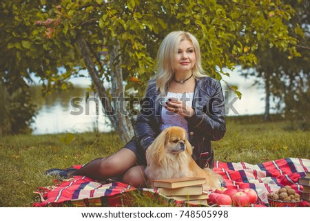 A dog is a human best friend. Pekingese light red color resting in the field in the grass with his owner sit at the plaid, enjoying of rays of the autumn warm sun