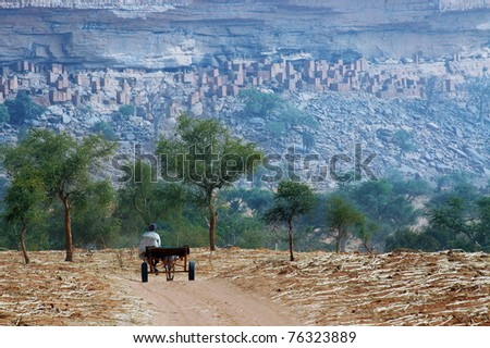 A Dogon man with donkey and cart approaching a village at the base of the Bandiagara escarpment in Mali - stock photo