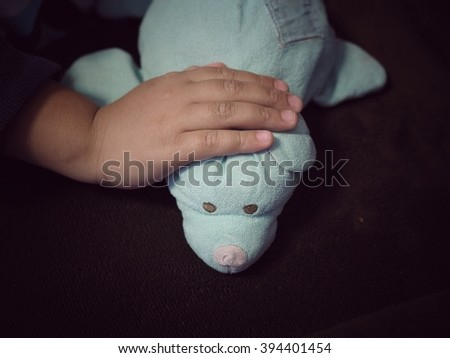 A doll is a child's best friend. Kids hand softly touch on the doll. - stock photo