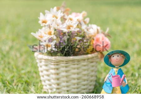 A doll standing holding water can on green grass background with flowerpot in a vintage retro style, with the sunrise, for the day of comfortable - stock photo
