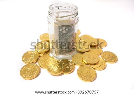 A dollar in bottle beside gold coins on isolated white background