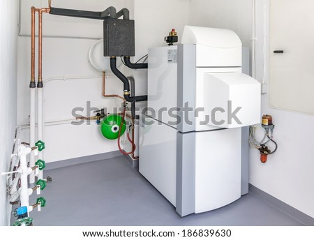 A domestic household boiler room with a new modern heating oil warm water system and pipes - stock photo
