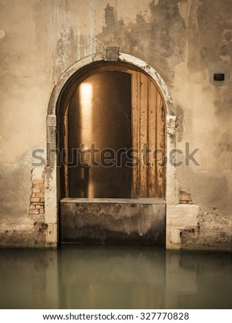 A door on a canal in Venice, Italy with water. - stock photo