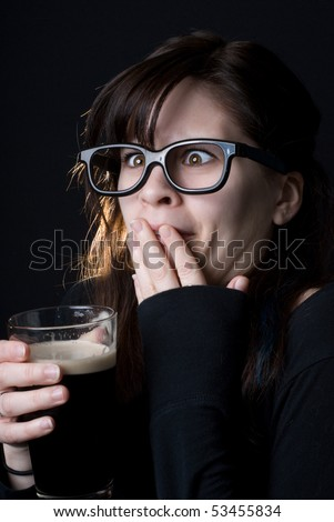 A dorky girl with goofy glasses on black background drinking a beer and making a face like it's not very good.