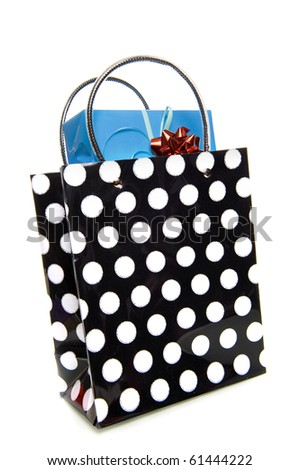 a dotted black and white bag with a blue present on a white background - stock photo