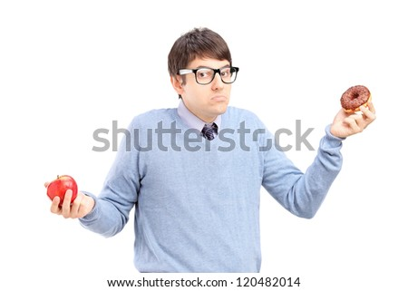 A doubtful guy holding an apple and donut trying to decide which one to eat - stock photo