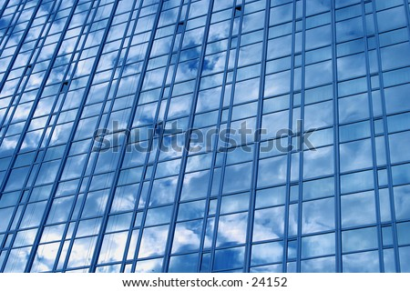 A downtown sky scraper reflecting a blue sky and clouds.