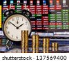 A downtrend columns of golden coins with an alarm clock. Financial chart as background. Selective focus - stock photo