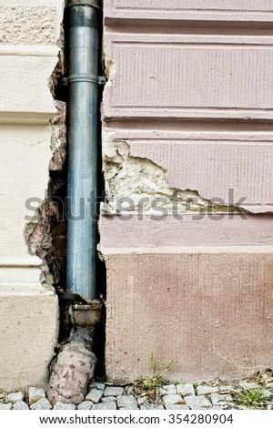 A drainpipe in a damaged strone wall - stock photo