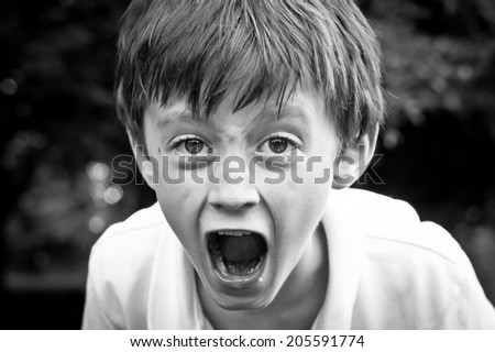 A dramatic monochrome image of an angry six year old boy - stock photo
