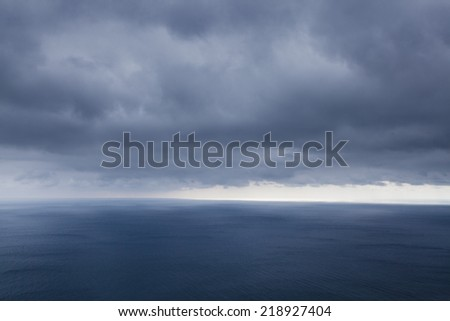 A dramatic seascape. Beams of the sun make the way through clouds and fall on the sea. - stock photo