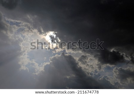 A dramatic shot of the sky with sun peaking through the clouds.  - stock photo