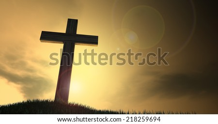 A dramatic silhouette of a wooden crucifix on top of a grassy hill on a warm sunrise morning