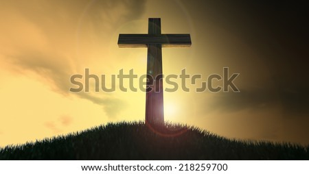 A dramatic silhouette of a wooden crucifix on top of a grassy hill on a warm sunrise morning  - stock photo