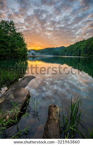 A dramatic sunset over Cranks Creek Lake in the Appalachian Mountains of Southeastern Kentucky. - stock photo