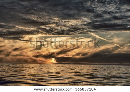 A dramatic sunset over the ocean in California shows the complex cloud patterns covering the setting sun. - stock photo