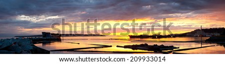 A dramatic sunset with clouds over rusty freighters acting as a breakwater for a harbor - Powell River, British Columbia, Canada.  - stock photo