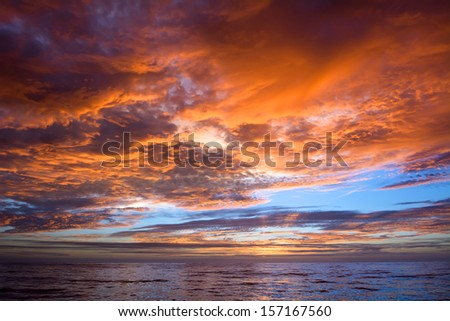 A dramatic, vibrant sunset over a calm ocean in Mexico - stock photo