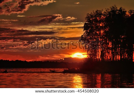 A dramatic view of the setting sun on the background of the river with glare and reflection on water, the silhouette of the island. - stock photo