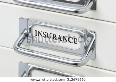 A drawer cabinet with the label Insurance - stock photo