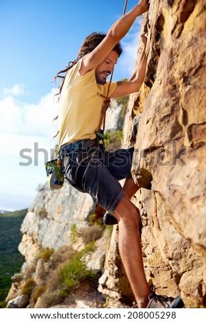 A dreadlock rock climbing guy finding a foothold on a steep mountain - stock photo