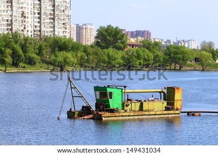 A dredger cleaning a lake from the silt - stock photo