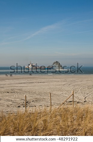 A dredger rain-bowing on the dutch coast - stock photo