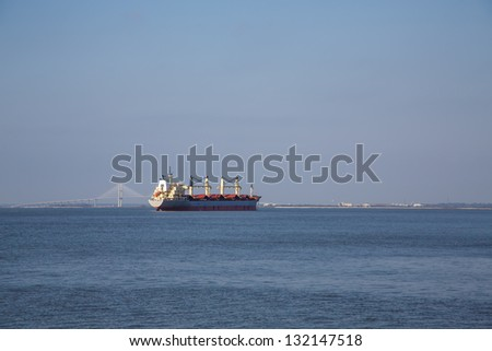 A dredging ship anchored in a harbor and working on the shipping lane