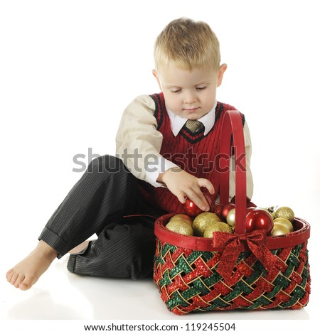 A dressed up but barefoot preschool boy taking Christmas bulbs from a red and green basket.  On a white background.