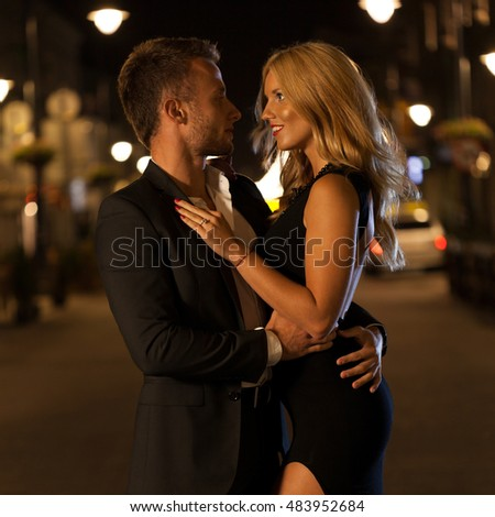 A dressed up couple embracing in a city at night