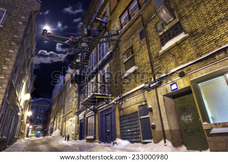 A drone with a camera is flying along a deserted street in a winter night. - stock photo