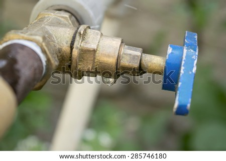 a drop of water dripping from the tap - stock photo