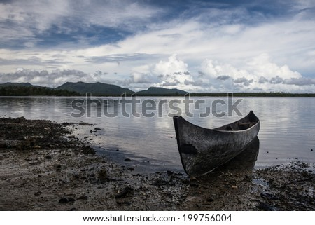 A dugout canoe lays on a remote beach in the Solomon Islands. Islanders throughout the Solomons still use canoes and outriggers as their main form of transportation. - stock photo